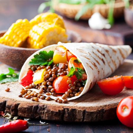 Vegan tortilla wrap, roll with grilled vegetables and lentil wooden background