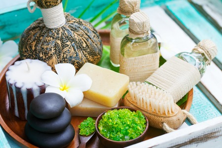 Spa and wellness massage setting, candle, stones.