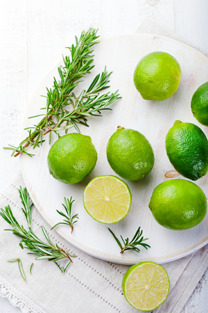 Fresh limes and rosemary on cutting board Top view