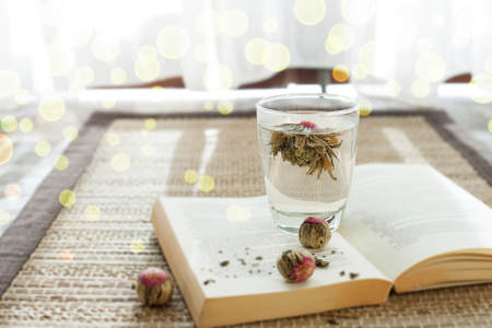Flower green tea in glass on a book. Copy space