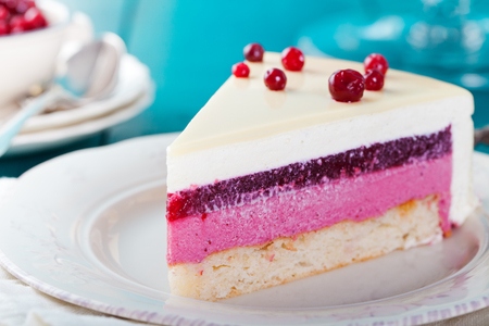 Cranberry, bilberry, raspberry tart, mousse cake, pie, cheesecake with fresh bilberries on a blue wooden background Stock Photo
