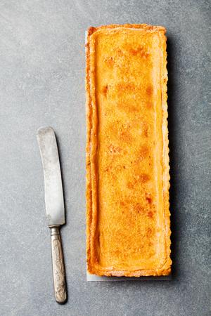 Caramel, creme brule tart. Grey stone background. Top view.