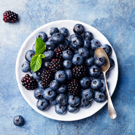 Blueberry and blackberry berries on a white plate on blue stone background. Top view.
