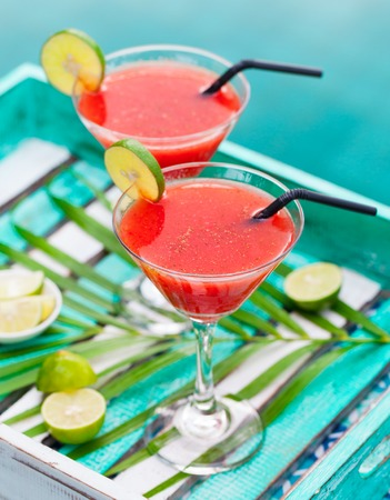 florida citrus: Strawberry margarita cocktail on colorful wooden background with palm leaf.