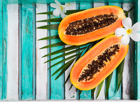 Papaya half on colorful wooden background with palm leaf. Top view. Copy space. Stock Photo