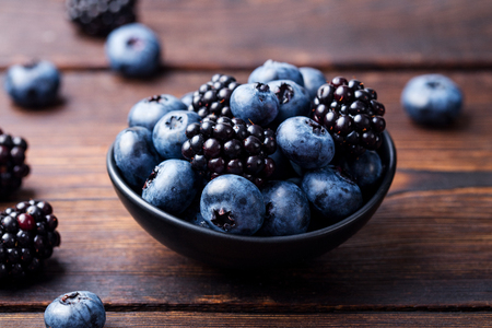 Blueberries, blackberries in black bowl on wooden background.
