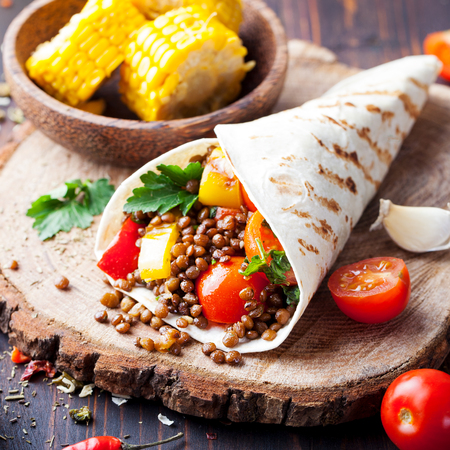 Vegan tortilla wrap, roll with grilled vegetables and lentil wooden background