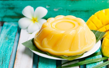 Mango pudding, jelly on white plate with palm leaf. Colorful wooden background.
