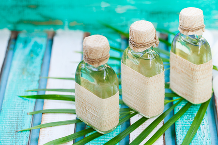 Massage oil set on colorful wooden background with palm leaf and flowers. Copy space
