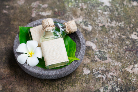 Massage oil on grey wooden background with flowers. Top view. Copy space.
