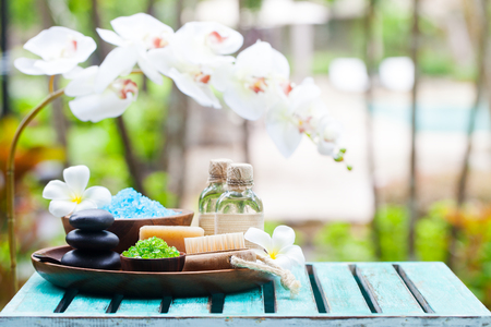 Spa and wellness massage setting. Still life with candle, towel and stones. Outdoor summer background. Copy space. Stock fotó