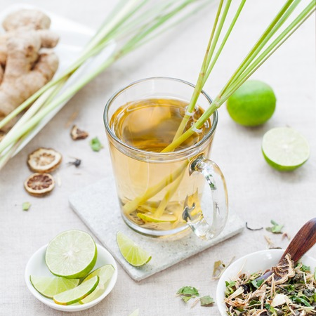 Herbal green tea with lemongrass and ginger in glass cup with fresh limes on textile background.
