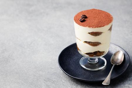 Tiramisu, traditional Italian dessert in glass on a grey stone background. Copy space. Archivio Fotografico