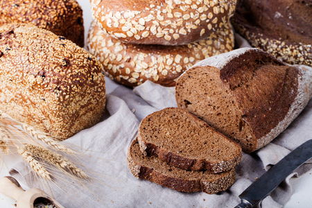 Fresh bread assortment on a textile background. Rustic background.