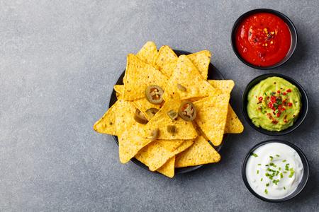 Nachos chips with dip variety on a wooden plate. Grey stone background. Standard-Bild