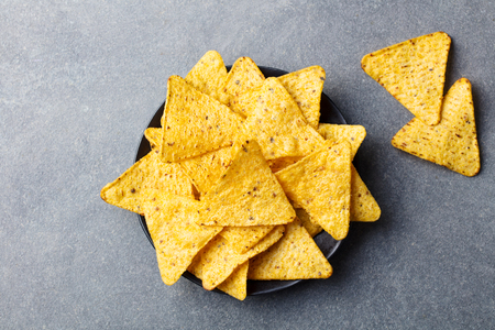 Nachos chips in bowl. Grey stone background. Top view