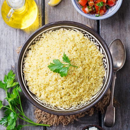 Couscous in bowl on a wooden background. Top view. Copy space. Stock Photo
