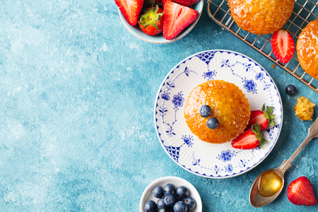 Muffin, cupcake with fresh berries on a plate. Blue background. Top view. Copy space.