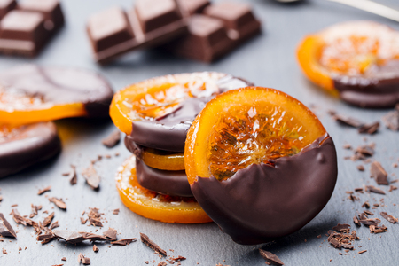 Candied orange slices in chocolate. Slate background. Stock Photo