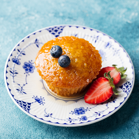 Muffin, cake with fresh berries on a plate. Blue background.