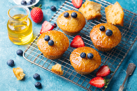 Muffins,cakes with fresh berries and honey on cooling rack. Stock Photo