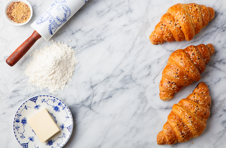 Croissants with baking ingredients. Traditional French pastry. Top view.