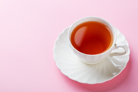 Tea in white cup on pink background. Copy space