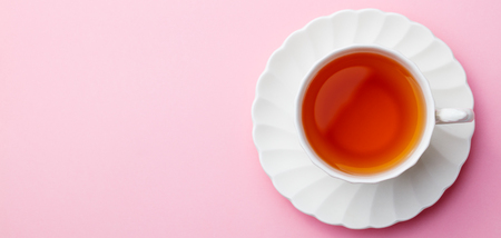 Cup of tea on pink background. Top view. Copy space.