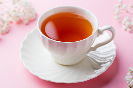 Cup of tea with fresh flowers on pink background. Copy space.