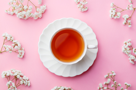 Cup of tea with fresh flowers on pink background. Top view. Copy space.