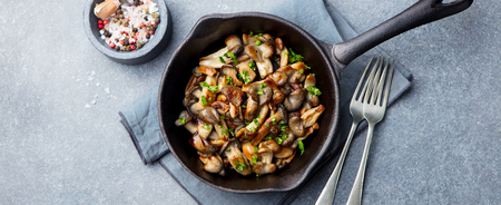 Fried mushrooms with fresh herbs in black cast iron pan. Top view.