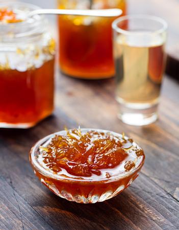 Orange, grapefruit confiture, jam in a glass jar. Wooden background Stock Photo