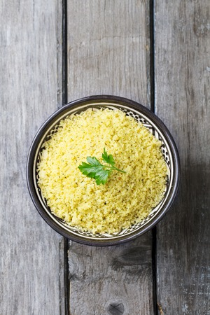 Couscous in bowl. Wooden background. Top view. Copy space