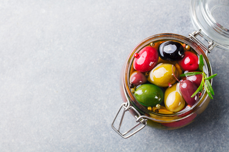 Olives assortment in glass jar with oil. Top view. Copy space