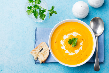 Pumpkin and carrot soup with cream and parsley on blue stone background. Top view. Copy space. Stock Photo