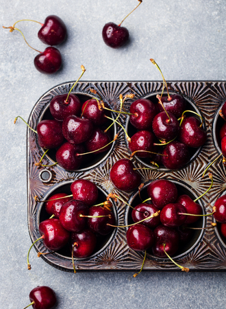 Fresh ripe black cherries in vintage backing dish on a stone background. Top view
