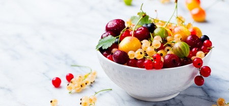 Assortment of fresh berries in white bowl. Marble background. Copy space. Stockfoto