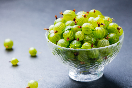 Gooseberries in glass bowl on black stone slate background. Copy space