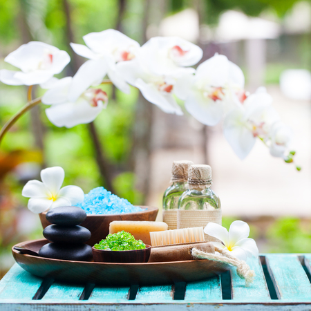 Spa and wellness massage setting. Still life with candle, towel and stones. Outdoor summer background. Copy space