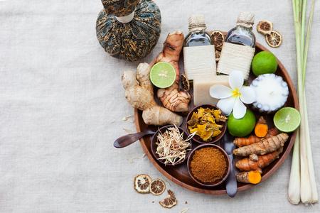 Spa, cuidado de la salud conjunto de aceites esenciales, jabón, jengibre, raíces de cúrcuma y especias en una bandeja de madera. Vista superior
