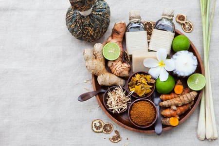 Spa, heath care set of essential oils, soap, ginger, turmeric roots and spices on a wooden tray. Top view