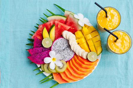 Tropical fruits assortment on a white plate with palm tree leaf with mango smoothie, textile blue background. Top view. Copy space.