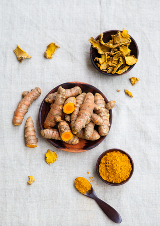 Fresh and dried turmeric roots in a wooden bowl. Grey textile background. Top view Stock Photo