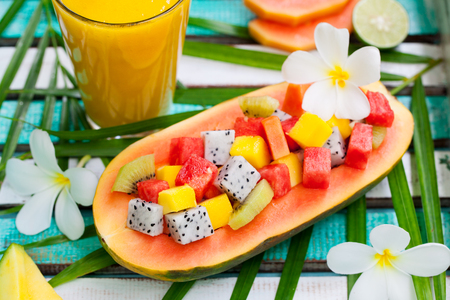 Tropical fruit salad in half of papaya with mango juice, smoothie on colorful wooden background. Top view.