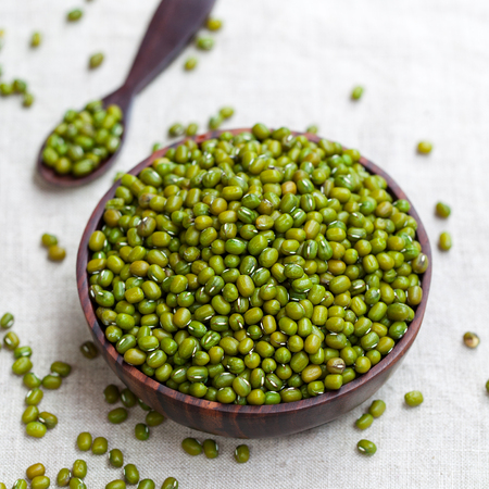Mung bean, green moong dal in wooden bowl. White textile background. Top view Stock Photo