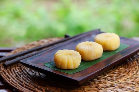 Mochi japanese dessert with mango on wooden plate Outdoor garden background 스톡 콘텐츠
