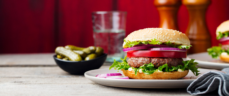 Burger on a plate. Wooden background. Copy space Stock Photo