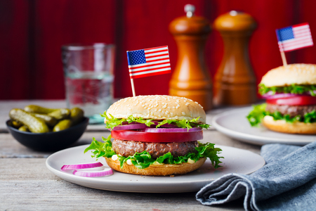 Burger on a plate with pickles. Wooden background