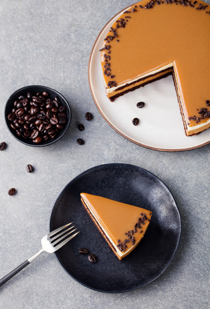 Caramel cake, mousse dessert on a plate. Grey stone background. Top view Stock fotó