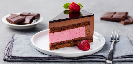 Chocolate and raspberry cake, mousse dessert on a white plate Stock Photo